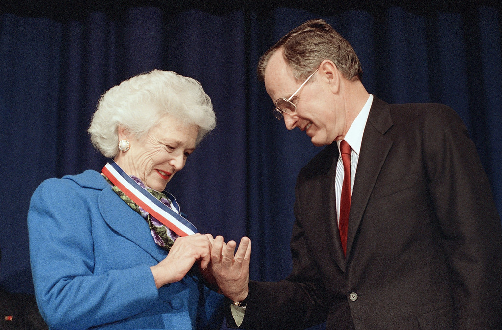 . U.S. President George Bush admires the Harry S. Truman Award for distinguished service that first lady Barbara Bush received from the Association of Community and Junior Colleges at their convention in Washington, Thursday, March 30, 1989. (AP Photo/Barry Thumma)