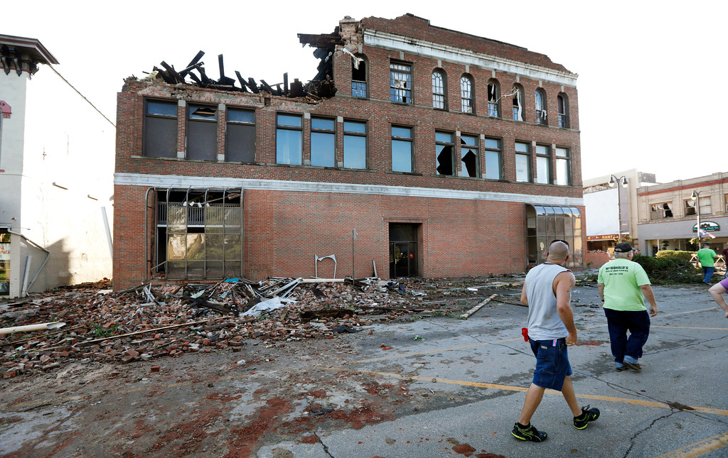 . Local residents walk past a tornado-damaged building on Main Street, Thursday, July 19, 2018, in Marshalltown, Iowa. Several buildings were damaged by a tornado in the main business district in town including the historic courthouse. (AP Photo/Charlie Neibergall)