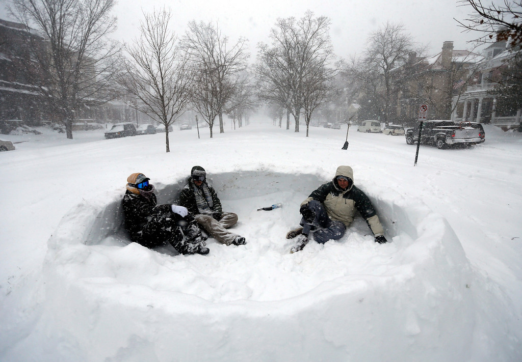 . Tyler Ridge, left, Evan Oakes, and Stephen Biggs, relax in a snow fort in the median of Monument Avenue in Richmond, Va., Saturday, Jan. 23, 2016. A massive winter storm buried much of the U.S. East Coast in a foot or more of snow by Saturday, shutting down transit in major cities, stranding drivers on snowbound highways, knocking out power to tens of thousands of people. (AP Photo/Steve Helber)