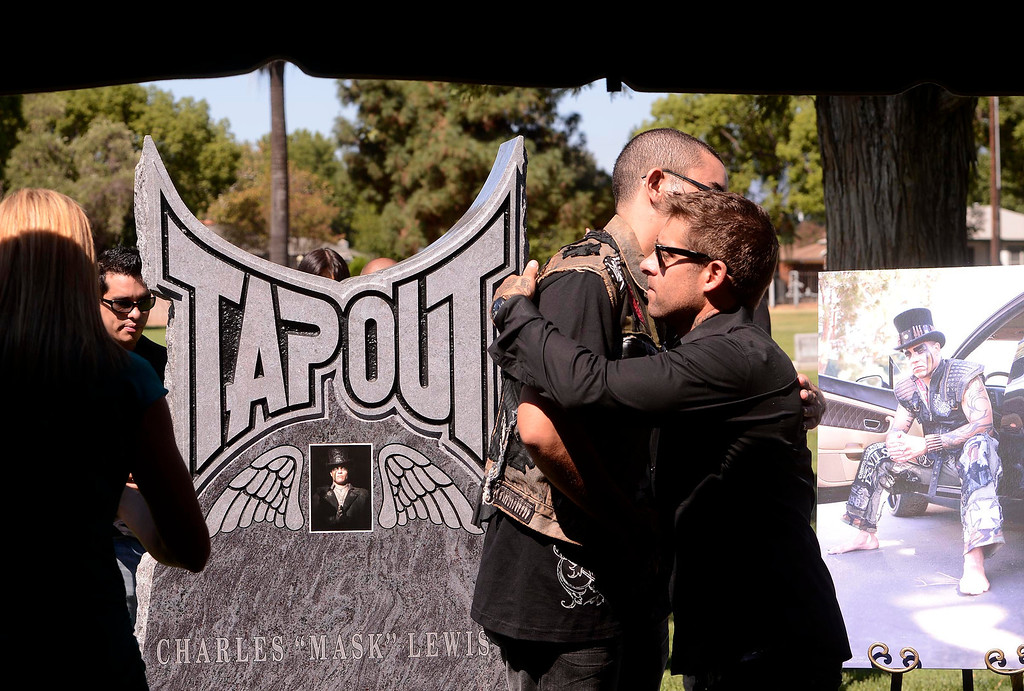 . Boaz Lewis, 20, of Riverside, center left, is hugged by Tapout president and co-founder Dan Caldwell during a tribute for Charles Lewis Jr. at Mountain View Cemetery in San Bernardino, CA on Saturday September 7, 2013.  Lewis was killed by a drunk driver in March of 2009.  (Photo by Gabriel Luis Acosta/San Bernardino Sun)