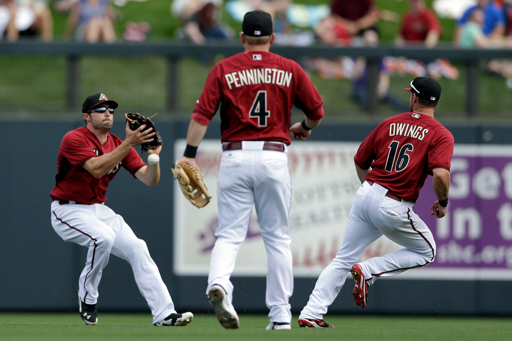 . Arizona Diamondbacks center fielder A.J. Pollock, left, misses the catch off a hit by Colorado Rockies\' Brandon Barnes as shortstop Cliff Pennington (4) and shortstop Chris Owings (16) watch during the fifth inning of a spring training baseball game Friday, Feb. 28, 2014, in Scottsdale, Ariz. (AP Photo/Gregory Bull)