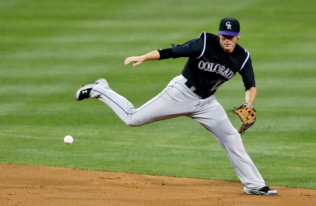 . Colorado Rockies shortstop Josh Rutledge can\'t manage a flip throw to second trying to get the force out after fielding a grounder behind second base hit by Abraham Almonte in the second inning of a baseball game Tuesday, Aug. 12, 2014, in San Diego. (AP Photo/Lenny Ignelzi)