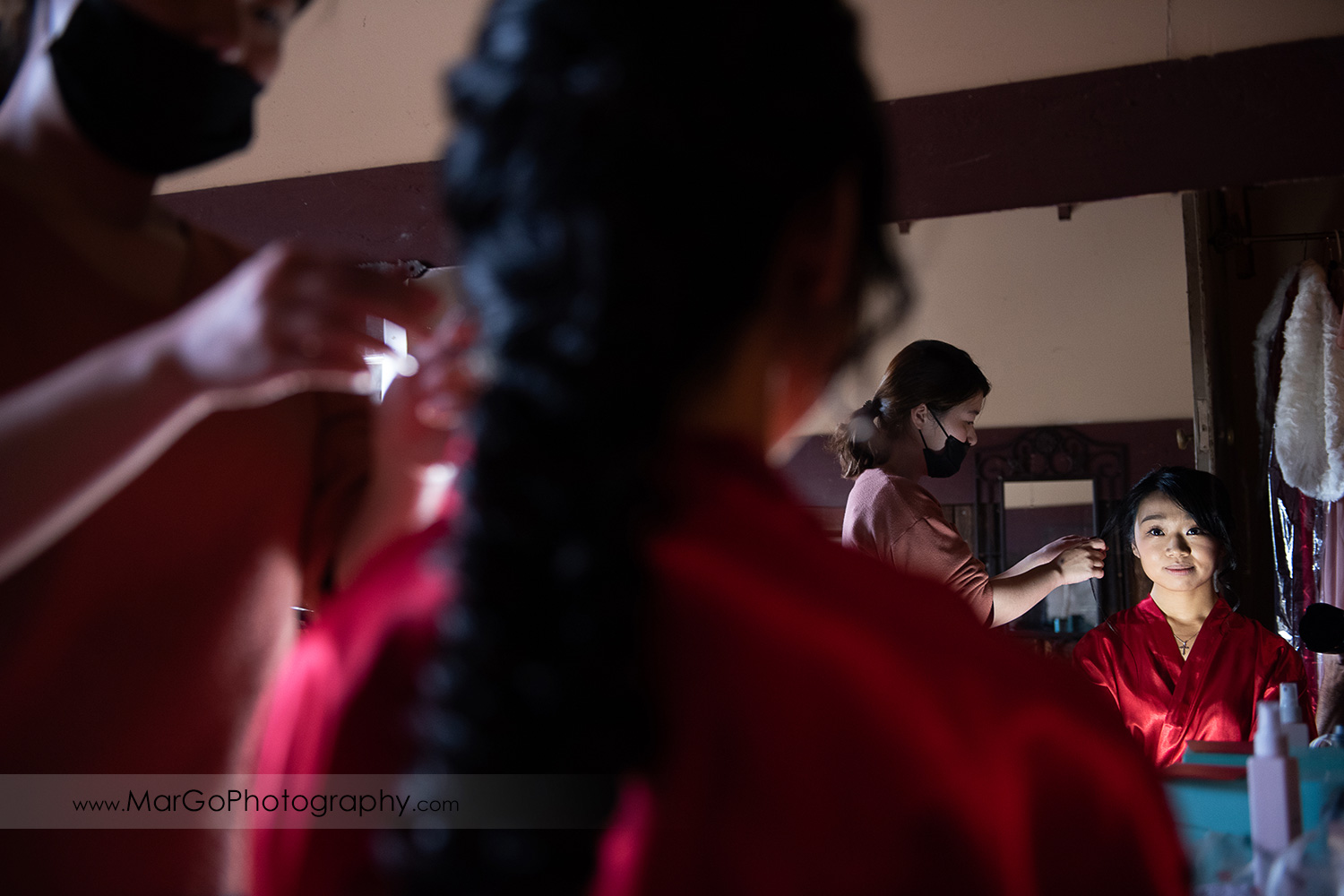 bride in red robe getting ready in front of mirror at Long Branch Saloon & Farms in Half Moon Bay