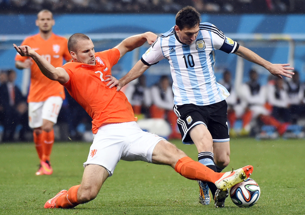 . Netherlands\' defender Ron Vlaar (L) and Argentina\'s forward and captain Lionel Messi vie for the ball during the semi-final football match between Netherlands and Argentina of the FIFA World Cup at The Corinthians Arena in Sao Paulo on July 9, 2014. (FABRICE COFFRINI/AFP/Getty Images)