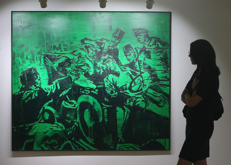 . A visitor looks at a painting that depicts Serbian secessionist Gavrilo Princip (L) assassinating Austrian Archduke Franz Ferdinand and his wife Duchess Sophie in a gallery at the mock-village of Andricgrad on St. Vitus Day in Srpska Republika on June 28, 2014 in Visegrad, Bosnia and Herzegovina. Serbian leaders held ceremonies at Andricgrad earlier in the day to mark the centenary of the 1914 assassination of the Archduke, an event that propelled Europe into World War I. The city of Sarajevo is holding its own commemoration, though Serbian leaders are boycotting the Sarajevo events, claiming the Bosniaks have turned the commemoration too partisan. Andricgrad was built by Serbian film director Emir Kusturica and will become the set for a film about Yugoslav poet Ivo Andric.  (Photo by Sean Gallup/Getty Images)