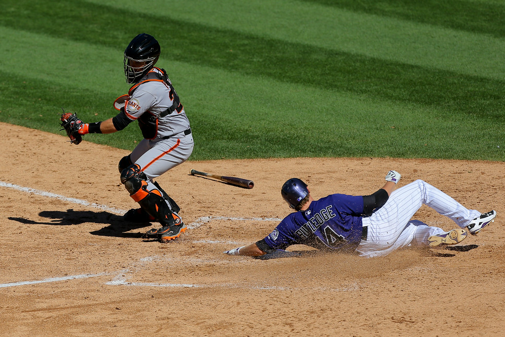 . DENVER, CO - SEPTEMBER 3:  Josh Rutledge #14 of the Colorado Rockies scores ahead of the tag attempt by catcher Buster Posey #28 of the San Francisco Giants during the sixth inning at Coors Field on September 3, 2014 in Denver, Colorado. (Photo by Justin Edmonds/Getty Images)
