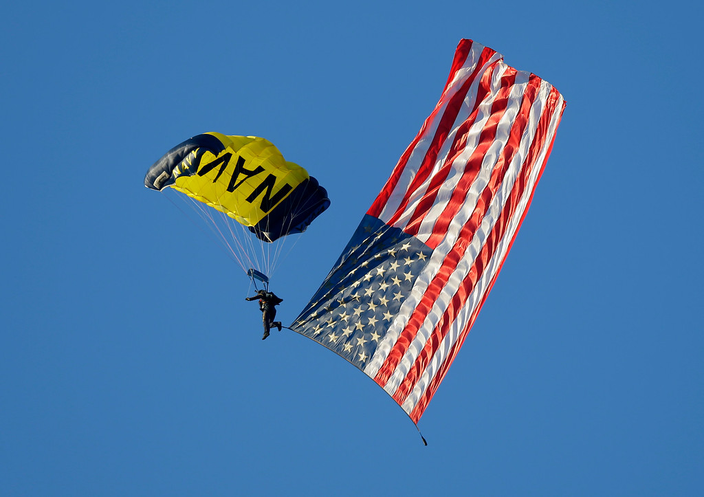 . A member of the U.S. Navy Parachute Team parachutes into Notre Dame Stadium with a U.S. flag before an NCAA college football game between Notre Dame and Michigan in South Bend, Ind., Saturday, Sept. 6, 2014. (AP Photo/Michael Conroy)