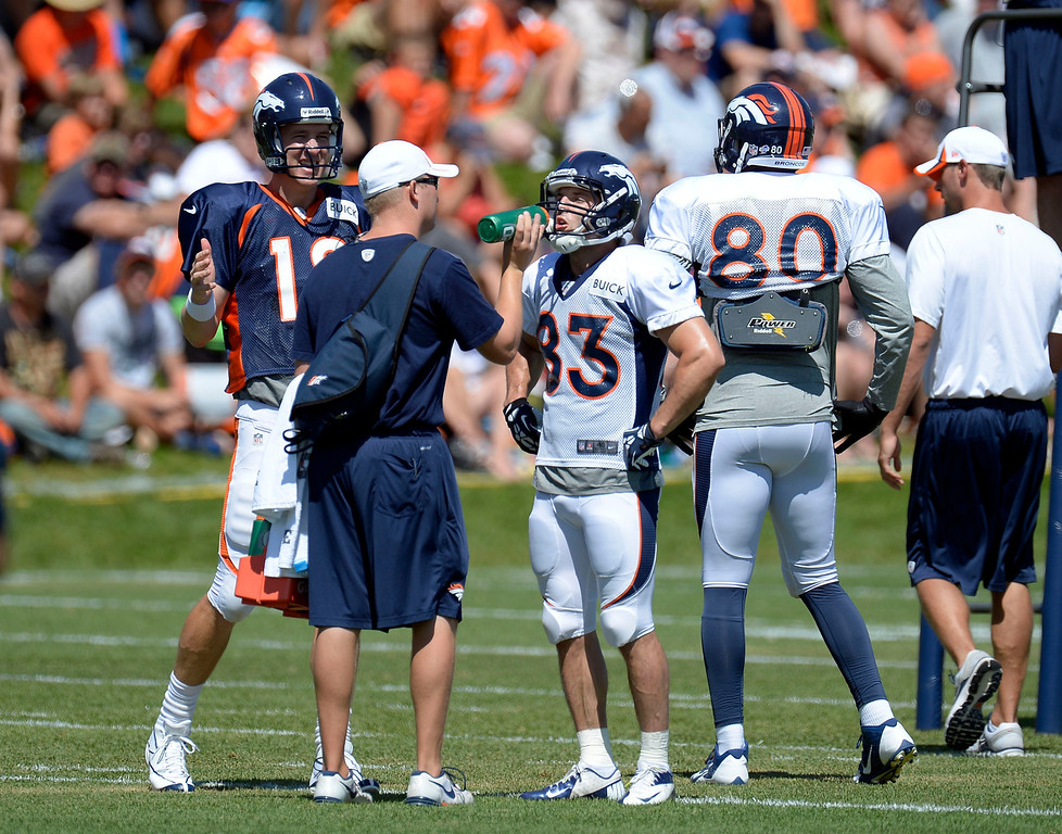 . Denver Broncos QB Peyton Manning (18) talks with TE Julius Thomas (80) as WR Wes Welker (83) take a water break during training camp August 5, 2013 at Dove Valley. (Photo By John Leyba/The Denver Post)