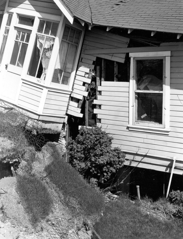 . Alaska Earthquake March 27, 1964. Wrecked dwelling astride boundling fracture, L Street graben at Eighth Avenue and N Street in Anchorage. The damage was caused entirely by ground displacement along the fracture. Photo by W.R. Hansen, U.S. Geological Survey