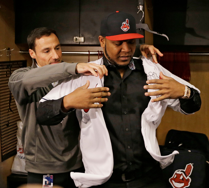 . Cleveland Indians president of baseball operations Chris Antonetti helps Edwin Encarnacion with his jersey, Thursday, Jan. 5, 2017, in Cleveland. One win from a World Series baseball title last season, the Indians finalized a $65 million, three-year contract with free agent slugger Encarnacion. (AP Photo/Tony Dejak)