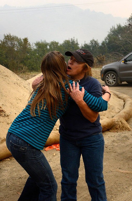 . Tori Chesebrough-Buckles, right, hugs Sharlene Bradford near the entrance to Pfeiffer Ridge Road as firefighters battle a wildland fire in the area in Big Sur, Calif. on Monday December 16, 2013. The women have a relative who lives up the road.(Photo David Royal/ Monterey County Herald)