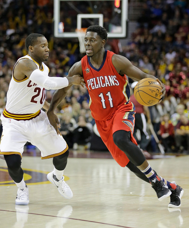 . New Orleans Pelicans\' Jrue Holiday (11) drives against Cleveland Cavaliers\' Kay Felder (20) in the second half of an NBA basketball game, Monday, Jan. 2, 2017, in Cleveland. (AP Photo/Tony Dejak)