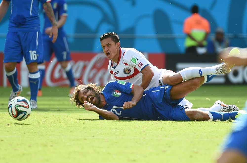 . Costa Rica\'s midfielder Jose Miguel Cubero (top) and Italy\'s midfielder Andrea Pirlo vie for the ball during a Group D football match between Italy and Costa Rica at the Pernambuco Arena in Recife during the 2014 FIFA World Cup on June 20, 2014. (EMMANUEL DUNAND/AFP/Getty Images)