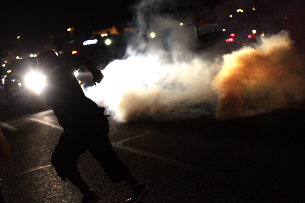 . A demonstrators protesting the death of Michael Brown runs amid tear gas used by police August 17, 2014 in Ferguson, Missouri. Tensions still run high in the Ferguson community after 18 -year-old Michael Brown was killed by a Ferguson police officer August 9 on Canfield Drive.  (Photo by Joshua Lott/Getty Images)
