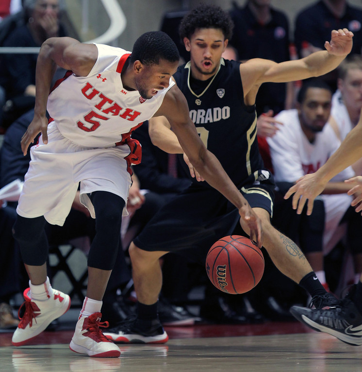 . Utah guard Jarred DuBois (5) works to control a loose ball against Colorado guard Askia Booker, right, in the second half during an NCAA college basketball game Saturday, Feb. 2, 2013 in Salt Lake City. Utah beat Colorado 58-55. (AP Photo/Steve C. Wilson)