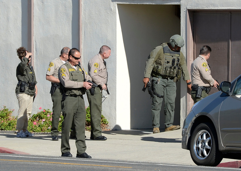 . A man in handcuffs eluded Sheriff\'s deputies before finally being caught hiding in a trash can in the alley behind the 700 block of 10th Street in San Pedro Wednesday, December 03, 2013. Deputies search door-to-door along Cabrillo Ave. with guns drawn looking for the suspect, who was found a half block away. Photo by Steve McCrank/DailyBreeze