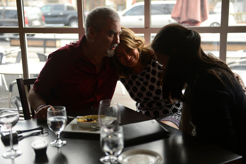 """. Owner Tammy Cunningham, (center) hugs Loren Danforth as he and his wife Kathy have their dessert. They are the last reservation to ever be served at Strings Restaurant on the last day of service as the Denver favorite closes April 30, 2013 Denver, Colorado. \""""This was our go to place if it was something special, said Loren. We had out 5th and 10th anniversary here. We\'ve been coming here since it opened, we always felt like family.\""""  (Photo By Joe Amon/The Denver Post)"""