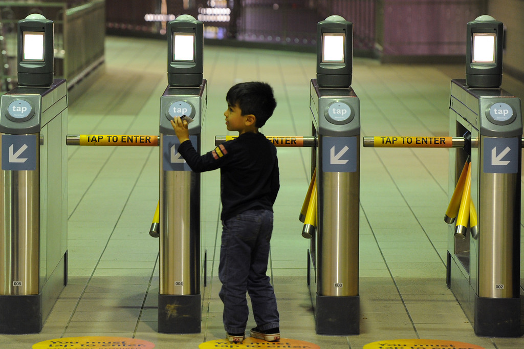 . A child places his ticket on the sensor at the turnstiles at the Union Station metro subway, Tuesday, June 18, 2013. (Michael Owen Baker/Staff Photographer)