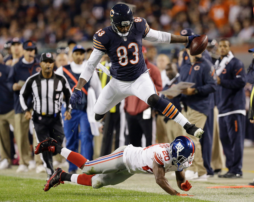 . Chicago Bears tight end Martellus Bennett (83) leaps over New York Giants cornerback Prince Amukamara (20) in the first half of an NFL football game, Thursday, Oct. 10, 2013, in Chicago. (AP Photo/Nam Y. Huh)