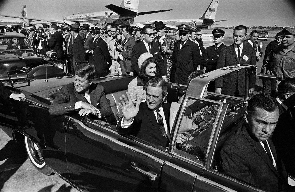 . Texas Gov. John Connally waves as the Connallys and Kennedys set off on what would be the president\'s final ride on Nov. 22, 1963. One of the modifications to the stock 1961 Lincoln Continental convertible was the addition of a middle row of jump seats. (Tom Dillard/Dallas Morning News/MCT)
