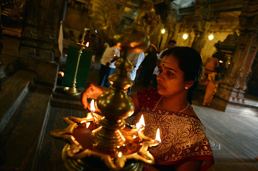 . A Sri Lankan Tamil devotee offers prayers while holding an oil lamp during Diwali, or the Festival of Lights at a Hindu temple in Colombo on November 2, 2013. The Hindu Festival of Lights, Diwali marks the homecoming of the God Lord Ram after vanquishing the demon king Ravana and symbolizes taking people from darkness to light in the victory of good over evil.  Ishara S.KODIKARA/AFP/Getty Images