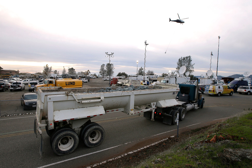 . A truck loaded with rocks arrives at the staging area as a helicopter takes off with a bag filled with rocks to be dropped on a hole on the lip of the Oroville Dam\'s emergency spillway Monday Feb., 13, 2017, in Oroville, Calif. The barrier, at the nation\'s tallest dam, is being repaired a day after authorities ordered mass evacuations for everyone living below the lake out of concerns the spillway could fail. (AP Photo/Rich Pedroncelli)