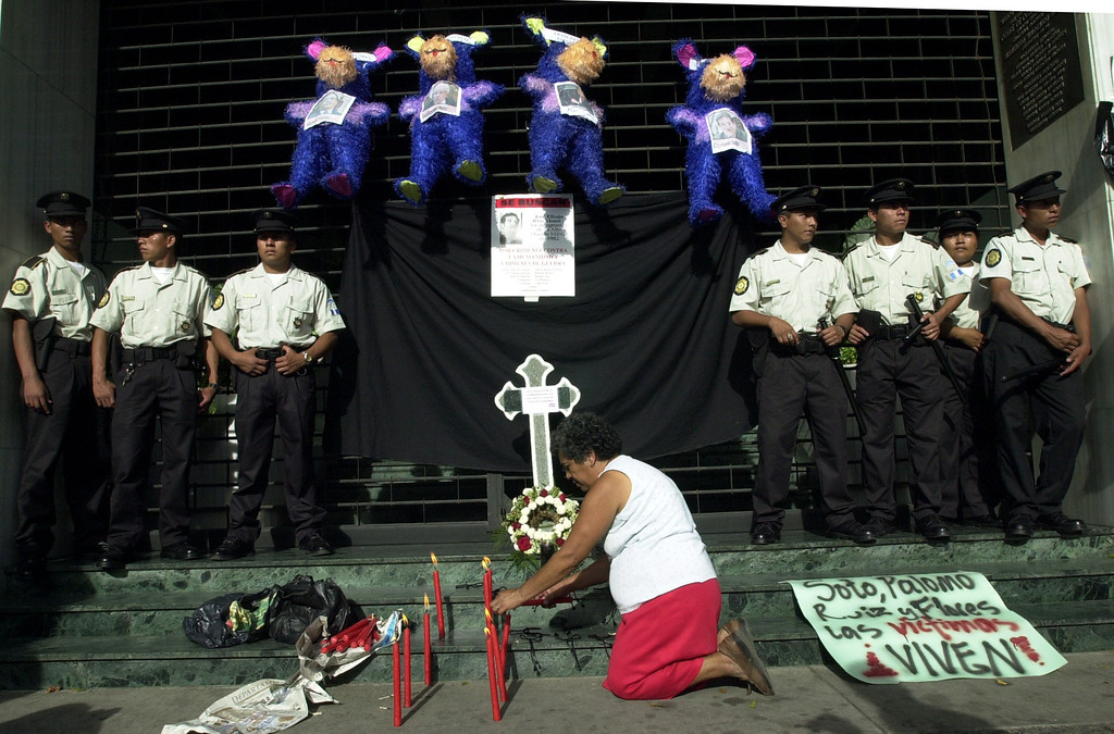 . Blanca de Hernandez lights candles outside of Guatemala\'s Constitutional Court as police look on, during a protest in Guatemala City Tuesday, July 15, 2003. Human rights groups acted with outrage and opposition politicians asked federal election officials Tuesday to ignore a decision by Guatemala\'s highest court allowing former dictator Efrain Rios Montt to run for president in November. (AP Photo/Rodrigo Abd)
