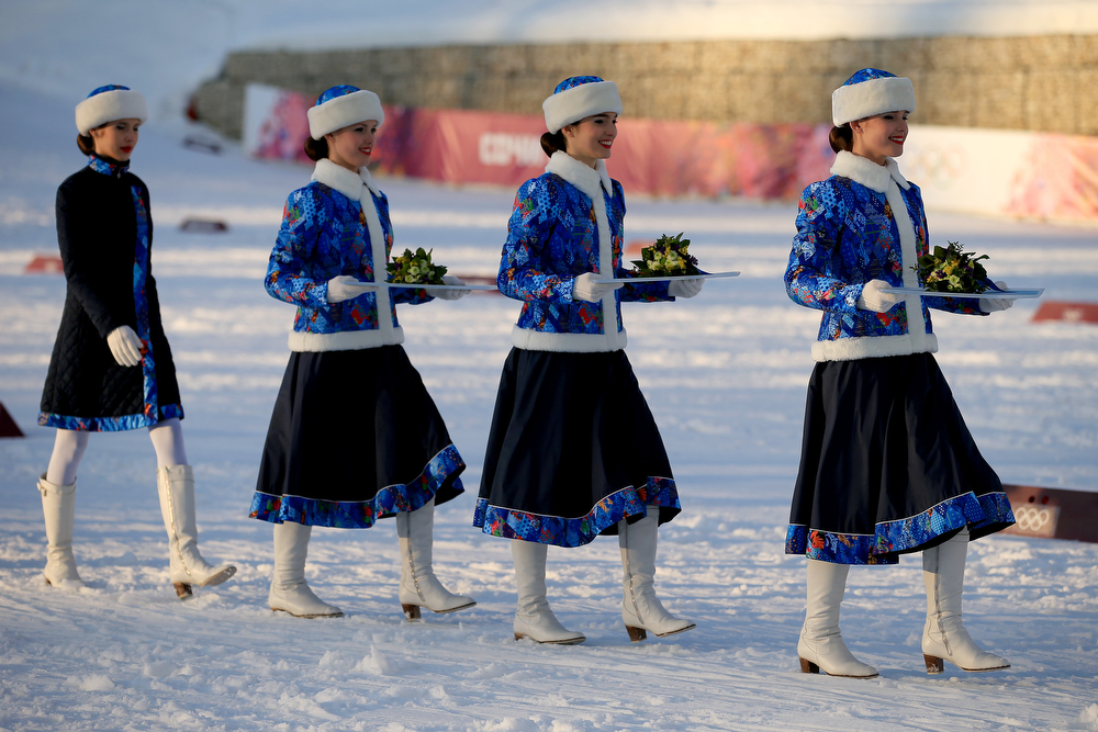. Flower bearers carry bouquets for the medalists during the flower ceremony for the Finals of the Ladies\' Sprint Free during day four of the Sochi 2014 Winter Olympics at Laura Cross-country Ski & Biathlon Center on February 11, 2014 in Sochi, Russia.  (Photo by Richard Heathcote/Getty Images)