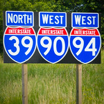 A row of Interstate Highway System shield signs indicating North I-39, West I-90, and West I-94