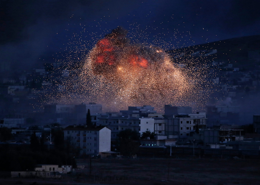 . Thick smoke and flames from an airstrike by the U.S.-led coalition rise in Kobani, Syria, as seen from a hilltop on the outskirts of Suruc, at the Turkey-Syria border, Monday, Oct. 20, 2014. Kobani, also known as Ayn Arab, and its surrounding areas, has been under assault by extremists of the Islamic State group since mid-September and is being defended by Kurdish fighters. (AP Photo/Lefteris Pitarakis, File)