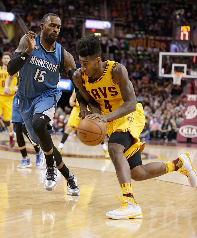 . Cleveland Cavaliers\' Iman Shumpert (4) drives past Minnesota Timberwolves\' Shabazz Muhammad (15) in the first half of an NBA basketball game Monday, Jan. 25, 2016, in Cleveland. (AP Photo/Tony Dejak)