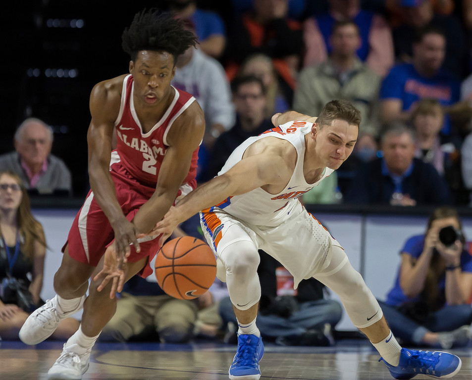 . Florida guard Egor Koulechov (4) and Alabama guard Collin Sexton (2) scramble for a loose ball during the first half of an NCAA college basketball game in Gainesville, Fla., Saturday, Feb. 3, 2018. Alabama won 68-50. (AP Photo/Ron Irby)