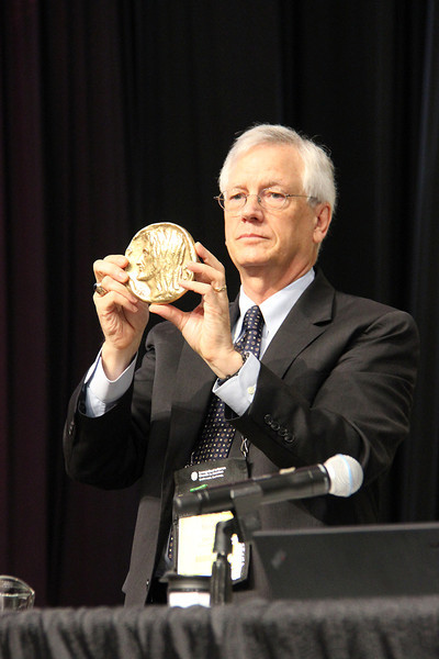 David Swartling, secretary of the ELCA, holds the Servus Dei Medal.