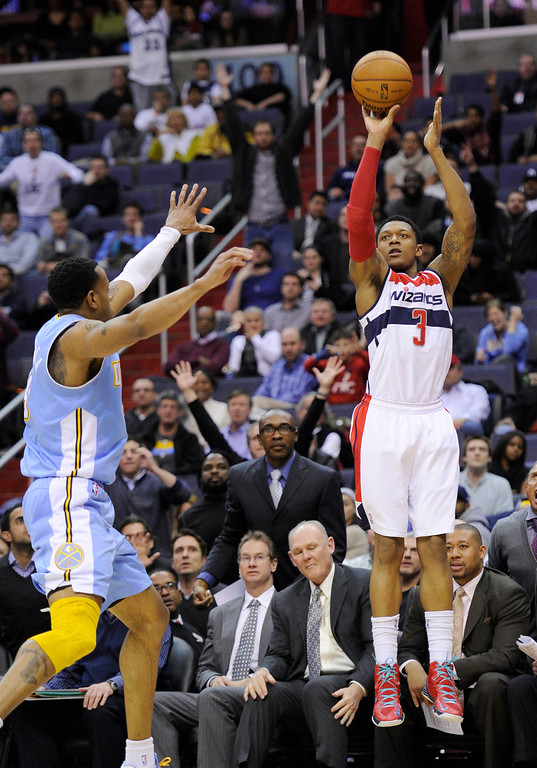 . Washington Wizards guard Bradley Beal (3) takes a shot against Denver Nuggets guard Andre Iguodala during the second half of an NBA basketball game, Friday, Feb. 22, 2013, in Washington. The Wizards won 119-113. (AP Photo/Nick Wass)