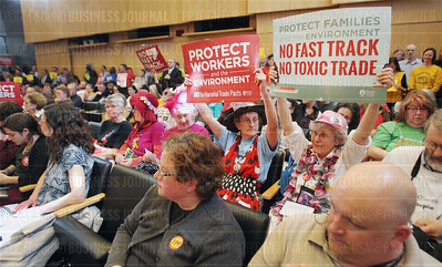 """""""Raging Grannies"""" Deejah Sherman-Peterson (right) and Annette Klapstein (center) of Seattle hold up signs protesting the TTP during public testimony to the City Council at Seattle City Hall in Seattle, Washington on March 30, 2015."""