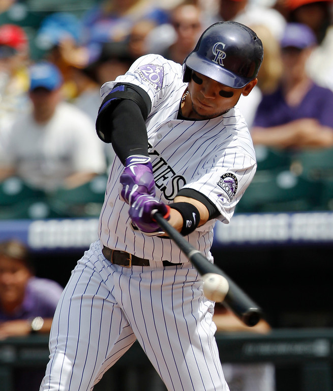 . Colorado Rockies\' Carlos Gonzalez connects for an RBI-double against the Philadelphia Phillies in the first inning of a baseball game in Denver, Saturday, June 15, 2013. (AP Photo/David Zalubowski)