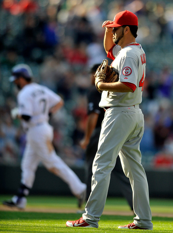 . St. Louis Cardinals relief pitcher Edward Mujica, right, reacts as Colorado Rockies\' Todd Helton rounds the bases after hitting a home run during the ninth inning of a baseball game on Thursday, Sept. 19, 2013, in Denver. (AP Photo/Jack Dempsey)