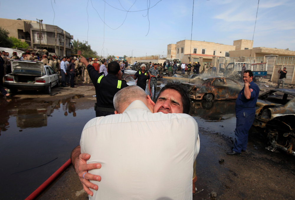 Description of . An Iraqi man is comforted at the scene of a car bomb attack in Baghdad, Iraq, Friday, March 29, 2013. A parked car bomb exploded near the al-Mahdi mosque in the northeastern Binook neighborhood as worshippers were leaving Friday prayers, killing and wounding several, just one of a string of bombings targeting Shiite mosques on Friday, killing and wounding dozens of people, police said.(AP Photo/Karim Kadim)