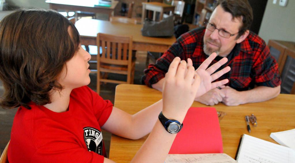 . Upper Elementary teacher Steve Kramer, right, listens as student Jay McPherson works with him on a math exercise. (Pioneer Press: John Doman)