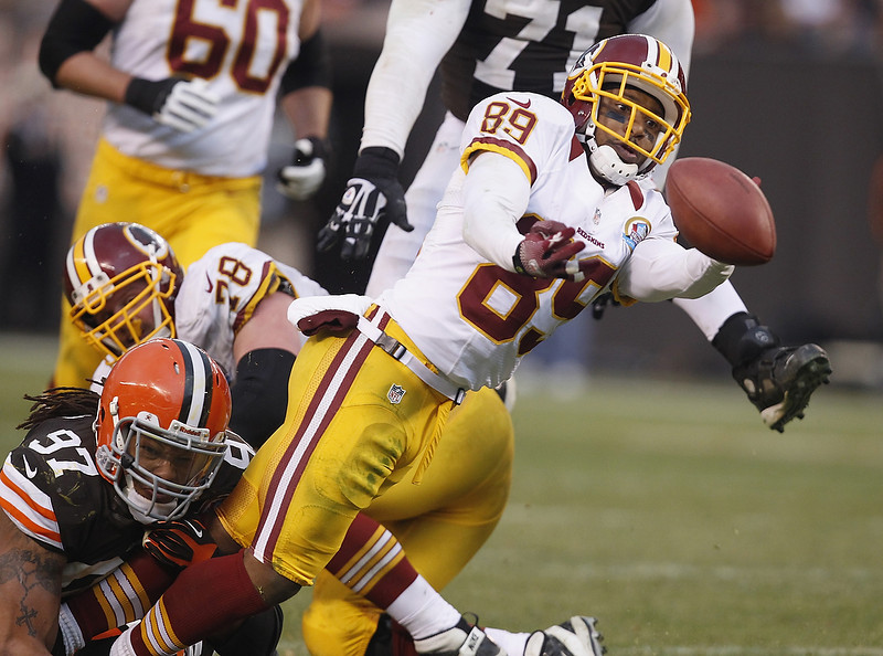 . Wide receiver Santana Moss #89 of the Washington Redskins fumbles the ball as he is hit by defensive lineman Jabaal Sheard #97 of the Cleveland Browns at Cleveland Browns Stadium on December 16, 2012 in Cleveland, Ohio.  (Photo by Matt Sullivan/Getty Images)