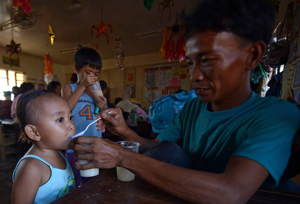 Description of . A man feeds his children at an evacuation center for victims of Typhoon Bopha in the town of Maparat in Compostela Valley province on December 8, 2012. Hungry and homeless typhoon survivors appealed for help on December 8 as the ravaged southern Philippines mourned its more than 500 dead and desperate people in one hard-hit town looted shops in search of food.     AFP PHOTO / TED  ALJIBE/AFP/Getty Images