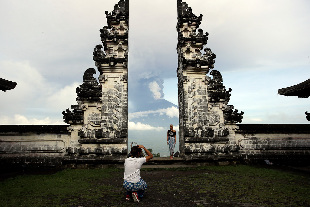 . A tourist poses for a photo with Mount Agung volcano erupting as they visit a temple in Karangasem, Indonesia, Monday, Nov. 27, 2017. Indonesian authorities raised the alert for a rumbling volcano on Bali to the highest level on Monday, stranding tens of thousands of travelers as ash clouds forced the closure of the tourist island\'s international airport. (AP Photo/Firdia Lisnawati)