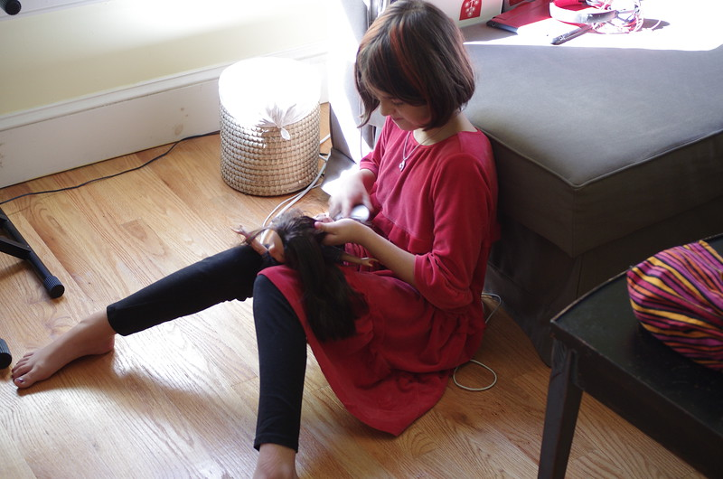 Guen brushes her doll's hair.