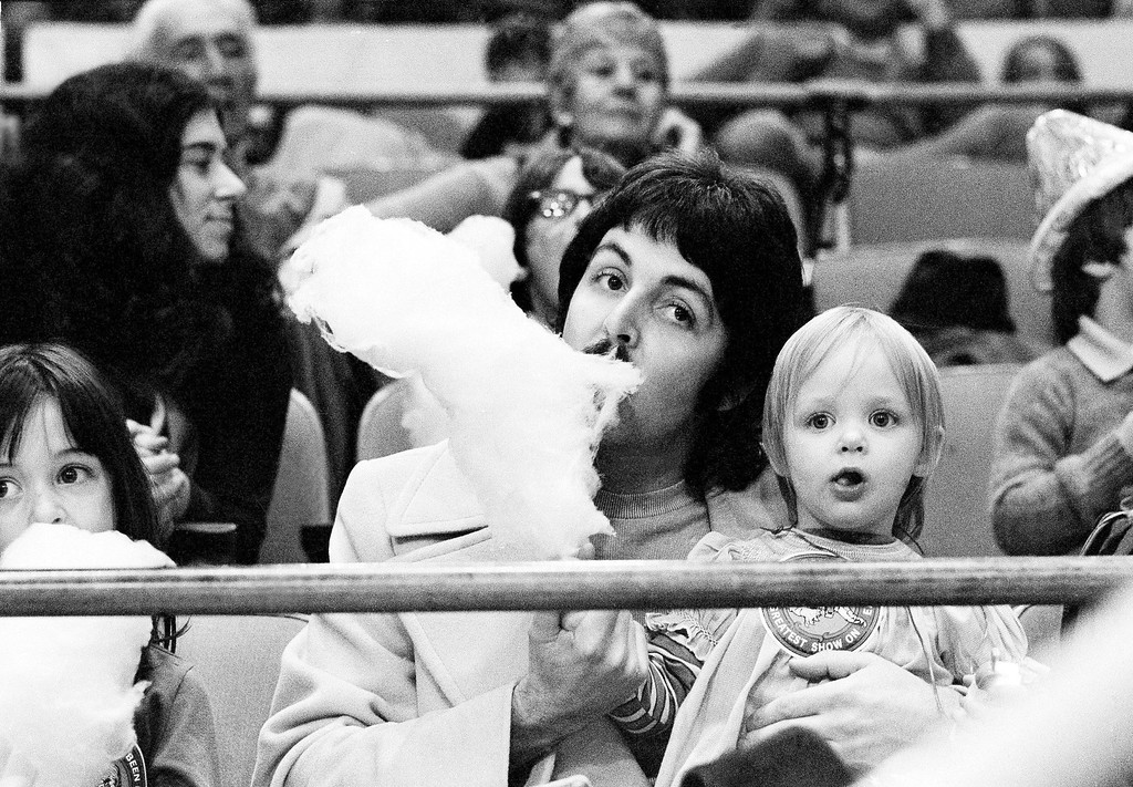 . Former Beatle Paul McCartney samples his young daughter Stella\'s cotton candy as the two sit on the sidelines at New York\'s Madison Square Garden, March 30, 1974, watching the Ringling Bros. & Barnum and Bailey Circus. (AP Photo/Suzanne Vlamis)