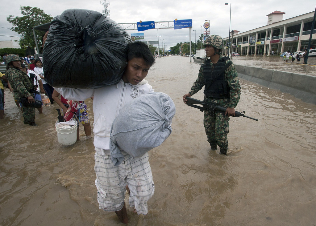 . A resident carrying belongings wades through a flooded street in Acapulco, state of Guerrero, Mexico, on September 17, 2013 as heavy rains hit the country. Mexican authorities scrambled Tuesday to launch an air lift to evacuate tens of thousands of tourists stranded amid floods in the resort of Acapulco following a pair of deadly storms. The official death toll rose to 47 after the tropical storms, Ingrid and Manuel, swarmed large swaths of the country during a three-day holiday weekend, sparking landslides and causing rivers to overflow in several states. Pedro PARDO/AFP/Getty Images