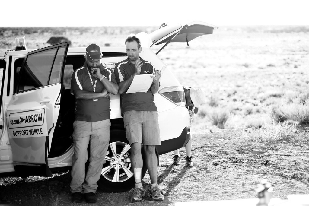 . ALICE SPRINGS, AUSTRALIA - OCTOBER 09:  (EDITORS NOTE: Image has been shot in black and white.) Darren Pearson and Cameron Tuesley from Team Arrow, Associated with Queensland University of Technology in Australia discuss details of of their car Arrow1 before racing on Day 4 on October 9, 2013 between Alice Springs and Kulgera, Australia. Over 25 teams from across the globe are competing in the 2013 World Solar Challenge - a 3000 km solar-powered vehicle race between Darwin and Adelaide. The race began on October 6th with the first car expected to cross the finish line on October 10th.  (Photo by Mark Kolbe/Getty Images)