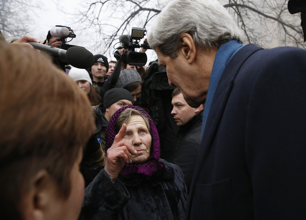 ". U.S. Secretary of State John Kerry clasps hands with an elderly woman who was speaking with him, during his visit to the Shrine of the Fallen in Kiev on March 4, 2014. The Shrine of the Fallen, located on Institutska Street, honors the fallen ""Heroes\"" of the \""Heavenly Sotnya\"" (Hundred). Over the course of the EuroMaidan protests, almost 100 protesters were killed by police. Most of them died on February 20 killed by sniper or automatic weapons fire on Institutska Street.  US Secretary of State John Kerry arrived in Kiev Tuesday for talks with Ukraine\'s new interim government, amid an escalating crisis in Crimea. His visit came as the United States said it would provide $1 billion to financially-stricken Ukraine as part of an international loan.  With the Black Sea peninsula of Crimea under near complete control by pro-Russian forces, US officials said Moscow could face sanctions within days. AFP PHOTO / POOL - Kevin LAMARQUE/AFP/Getty Images"