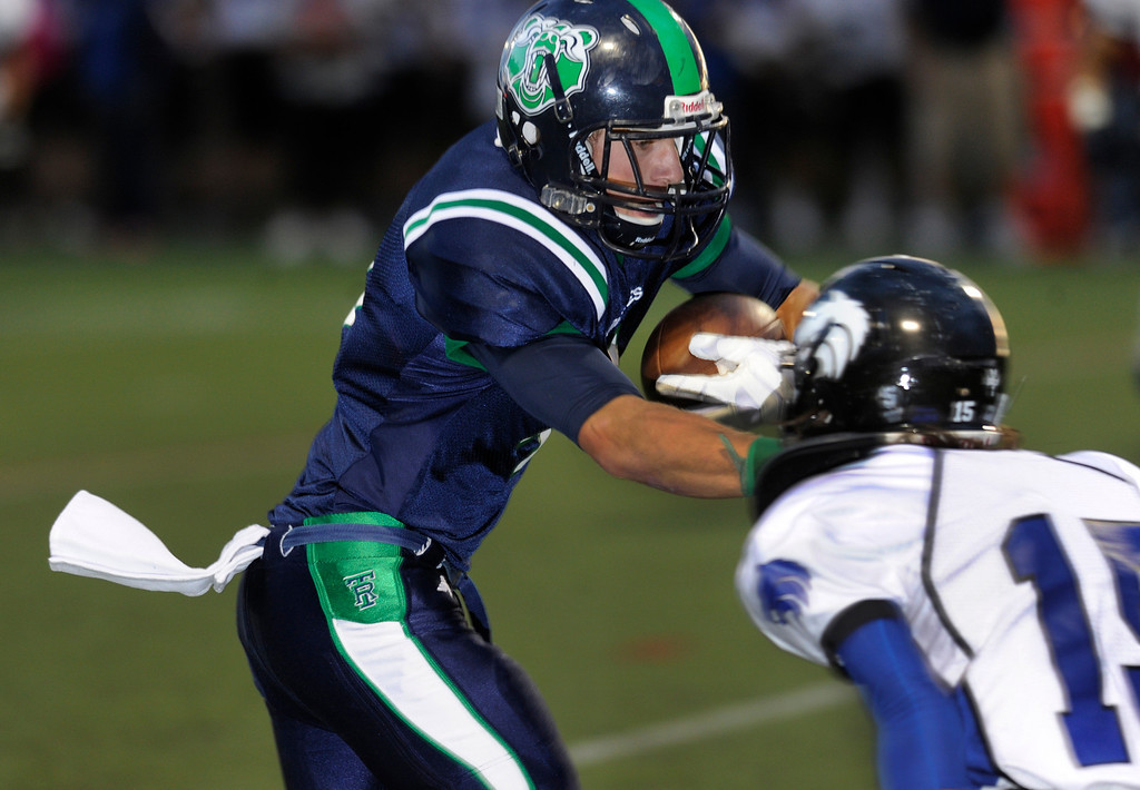 . HIGHLANDS RANCH, CO. - SEPTEMBER 13: Grizzlies\' wide receiver Mark Hopper (4) looked for room to run after a first quarter catch. Wolves\' defensive back Beau Martinez (15) made the tackle. The ThunderRidge High School football team hosted Grandview at Shea Stadium Friday night, September 13, 2013.  Photo By Karl Gehring/The Denver Post