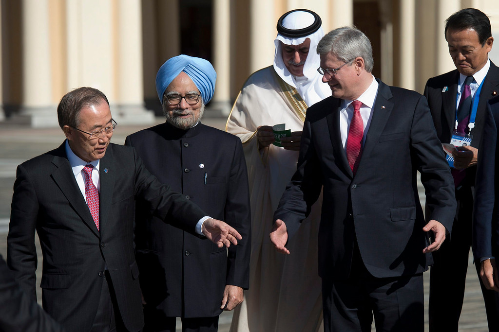 . Indian Prime Minister Manmohan Singh, center, looks on as Canadian Prime Minister Stephen Harper and United Nations Secretary-General Ban Ki-moon talk about where they are supposed to stand as the finance ministers from Saudia Arabia and Japan, Ibrahim bin Abdulaziz Al-Assaf and Taro Aso, back right, respectively, wait for the other leaders during the family photo at the G20 Summit Friday, Sept. 6, 2013, in St.Petersburg, Russia. (AP Photo/The Canadian Press, Adrian Wyld)