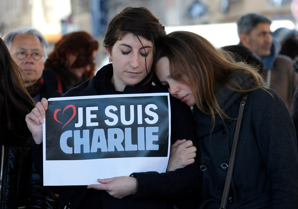 ". People pay tribute to the victims of the satirical newspaper ""Charlie Hebdo\"", in Marseille, southern France, Thursday, Jan. 8, 2015, a day after masked gunmen stormed the offices of a satirical newspaper and killed 12 people. French police hunted Thursday for two heavily armed men ó one with a terrorism conviction and a history in jihadi networks ó in the methodical killing of 12 people at a satirical newspaper that caricatured the Prophet Muhammad. Placard reads \""I am Charlie\"" . (AP Photo/Claude Paris)"